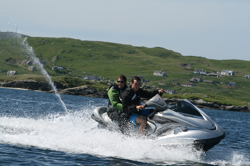 Two people flying along on a Jet Ski